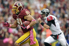 Washington Redskins outside linebacker Ryan Kerrigan (91) runs for a touchdown as Atlanta Falcons quarterback Matt Ryan pursues during the first half of an NFL football game in Landover, Md., Sunday, Oct. 7, 2012. (AP Photo/Evan Vucci)