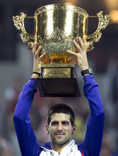 Serbia's Novak Djokovic holds the trophy after he won the men's singles final match against Jo-Wilfried Tsonga of France in the China Open tennis tournament in Beijing Sunday, Oct. 7, 2012. (AP Photo/Andy Wong)
