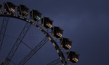 People ride the ferris wheel in an amusement park at the famous Bavarian