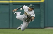 Oakland Athletics center fielder Coco Crisp bobbles a hit by Detroit Tigers' Miguel Cabrera allowing Tigers' Austin Jackson and Omar Infante to score during the seventh inning of Game 2 of the American League division baseball series, Sunday, Oct. 7, 2012, in Detroit. (AP Photo/Paul Sancya)