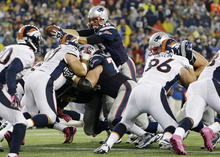 New England Patriots quarterback Tom Brady (12) goes up for a touchdown against the Denver Broncos in the third quarter of an NFL football game, Sunday, Oct. 7, 2012, in Foxborough, Mass. (AP Photo/Elise Amendola)