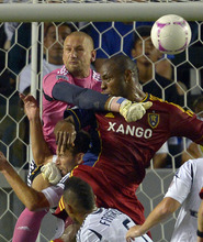 Los Angeles Galaxy goalkeeper Josh Saunders, left, punches a shot away from Real Salt Lake's Jamison Olave, right, as Galaxy's Rommy Meyer is squeezed in between during the first half of their MLS soccer match on Saturday, Oct. 6, 2012, in Carson, Calif. (AP Photo/Mark J. Terrill)