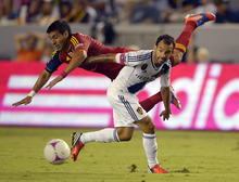 Real Salt Lake's Javier Morales, left, falls as he battles for the ball with Los Angeles Galaxy's Juninho during the first half of their MLS soccer match, Saturday, Oct. 6, 2012, in Carson, Calif. (AP Photo/Mark J. Terrill)