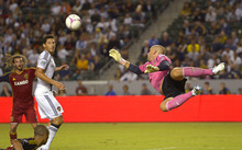 Los Angeles Galaxy goalkeeper Josh Saunders makes a save as Galaxy's Omar Gonzalez, center, and Real Salt Lake's Kyle Beckerman watch during the second half of an MLS soccer match, Saturday, Oct. 6, 2012, in Carson, Calif. Real Salt Lake won 2-1. (AP Photo/Mark J. Terrill)
