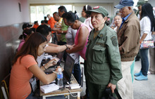 An elderly woman wearing a Bolivarian militia uniform stands before an election worker, who holds her identification as part of the voting process, before casting her ballot in the presidential election at a polling station in Caracas, Venezuela, Sunday, Oct. 7, 2012.  President Hugo Chavez is running against opposition candidate Henrique Capriles. The Bolivarian militia, created by Chavez, is estimated to number more than 100,000 who do not report to the armed forces. (AP Photo/Ariana Cubillos)
