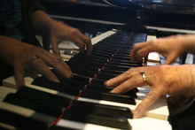 Scott Sommerdorf     The Salt Lake Tribune              Customer Clara Neu tries out the keys on one of the store's Steinways at Daynes Music Company in Midvale, Monday, October 1, 2012. The store will be celebrating the store's 150th anniversary.
