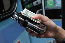In this Sept. 27, 2012 photo, a student hands over two electronic devices and payment of a dollar for each at the Pure Loyalty Electronic Device Storage truck parked near the Washington Irving educational complex in New York. Cellphones are banned in all New York City public schools, but the rule is widely ignored except in schools with metal detectors. Outside those schools, entrepreneurs park trucks where students drop off electronic devices before class and get them back at the end of the day.(AP Photo/Tina Fineberg)
