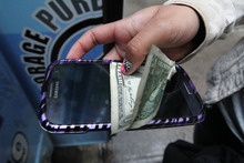 In this Sept. 27, 2012 photo, a student holds an electronic device along with payment of a dollar to store it for the day in the Pure Loyalty Electronic Device Storage truck parked near the Washington Irving educational complex in New York. Cellphones are banned in all New York City public schools, but the rule is widely ignored except in schools with metal detectors. Outside those schools, entrepreneurs park trucks where students drop off electronic devices before class and get them back at the end of the day.(AP Photo/Tina Fineberg)