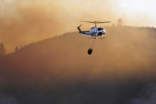 A helicopter heads toward the Okanogan River to pick up water Tuesday, Oct. 2, 2012 after previously dropping water on the St. Mary's fire burning about six miles from Omak, Wash. (AP Photo/The Omak-Okanogan County Chronicle, Roger Harnack)