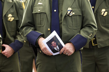 A Border Patrol agent holds a funeral program for slain U.S. Border Patrol agent Nicholas Ivie during services at The Church of Jesus Christ of Latter-day Saints meetinghouse in Sierra Vista, Ariz. Monday, Oct. 8, 2012. Ivie, a U.S. Border Patrol agent killed in an apparent friendly fire shooting with two other agents, is being remembered as a family man who loved his job and his colleagues. (AP Photo/The Arizona Republic, Michael Chow)