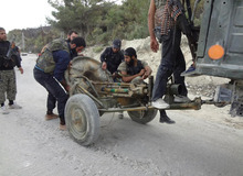 In this Sunday, October 7, 2012 citizen journalism image provided by Edlib News Network, ENN, which has been authenticated based on its contents and other AP reporting, Free Syrian Army fighters inspect a mortar captured from Syrian Army forces in the village of Khirbet al-Jouz, in the northern province of Idlib, Syria. The Turkish state-run Anadolu news agency said Sunday that the rebels had regained full control of Khirbet al-Jouz. (AP Photo/Edlib News Network ENN)