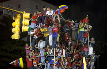 Supporters of President Hugo Chavez celebrate outside the Miraflores presidential palace  in Caracas, Venezuela, Sunday, Oct. 7, 2012. Venezuela's electoral council said late Sunday President Hugo Chavez has won re-election, defeating challenger Henrique Capriles.(AP Photo/Ramon Espinosa)