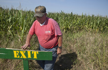 In this photo taken Tuesday, Oct. 2, 2012, Bob Schaefers checks a sign at his corn maze near Mayflower, Ark. Devastating spring freezes and this year's historic drought have taken some of the charm out of rustic fall destinations, leaving some corn mazes too short for labyrinth duty, orchards virtually devoid of U-pick apples and fall colors muted. (AP Photo/Danny Johnston)