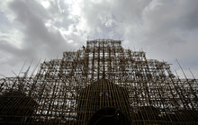An Indian laborer is seen atop a building under construction at the venue for the upcoming Durga Puja, or Durga Prayers festival in the eastern Indian city Bhubaneswar, India, Monday, Oct. 8, 2012. Seen as the mother of the universe, Durga is worshipped for her graciousness as well as her fearsome power. (AP Photo/Biswaranjan Rout)