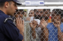 A police officer speaks with illegal immigrants behind a fence at a detention center in Komotini town, northern Greece, on Monday, Oct. 8, 2012. The government has toughened its stance on illegal immigration, with mass roundups and new detention centers paid for with the help of EU funds. Greece is the European Union's busiest transit point for illegal immigrants. Sign reads: Projects was funded 75 percent by the EU and 25 percent from national resources. (AP Photo/Nikolas Giakoumidis)