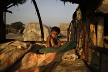 A Pakistani child, her face covered with flies, whose family was displaced from their village in Pakistan's Sindh province by flooding in 2010, waits for her sister to dress her, at their makeshift home, in a slum on the outskirts of Islamabad, Pakistan, Monday, Oct. 8, 2012. (AP Photo/Muhammed Muheisen)