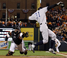 New York Yankees' Ichiro Suzuki, right, of Japan, leaps past Baltimore Orioles catcher Matt Wieters to score a run on a double by Robinson Cano in the first inning of Game 2 of the American League division baseball series on Monday, Oct. 8, 2012, in Baltimore. (AP Photo/Alex Brandon)