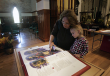 Kim Raff | The Salt Lake Tribune Louona Tanner, left, looks through Prophets with her granddaughter Sienna Pauli, one of the books in the reproduction of the Staint John's Bible on display at the Cathedral Church of St. Mark in Salt Lake City on Oct. 3, 2012. The bible was produced by Saint John's Abbey and University, Collegeville, Minnesota. Renowned calligrapher Donald Jackson and a team of fellow artists and scribes were commissioned to produce this hand-written, hand illuminated Bible whose seven volumes measure 2 feet tall and 3 feet wide when opened.
