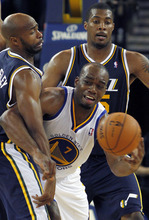 Golden State Warriors' Carl Landry passes around Utah Jazz's Jamaal Tinsley during the second half of a preseason NBA basketball game in Oakland, Calif., Monday, Oct. 8, 2012. Utah Jazz's Derrick Favors is behind Landry. The Warriors defeated the Jazz 83-80. (AP Photo/George Nikitin)