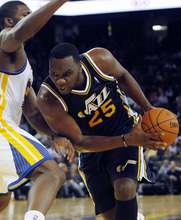 Utah Jazz Al Jefferson (25) drives for the basket past Golden State Warriors' Festus Ezeli during the second half of a preseason NBA basketball game in Oakland, Calif., Monday, Oct. 8, 2012. (AP Photo/George Nikitin)