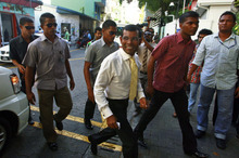 Maldives' former President Mohamed Nasheed walks escorted by policemen towards a court in Male, Maldives, Tuesday, Oct. 9, 2012. Nasheed was taken into custody Monday after he twice failed to appear in court to face charges that he illegally ordered the arrest of a judge while in office. Amnesty International says it is concerned by reports that police in the Maldives used excessive force when arresting Nasheed. (AP Photo/Sinan Hussain)