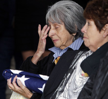 Delouise Guerra, sister of Marine  PFC James Jacques, wipes away tears during his funeral at Fort Logan National Cemetery in Denver on Tuesday, Oct. 9, 2012. Jacques funeral was held 37 years after he was killed during the rescue of the crew of an American cargo ship seized by Cambodia in May of 1975.  His remains were identified in August 2012. Guerra's sister-in-law, Mary Lee Jacques, sits at right.  (AP Photo/Ed Andrieski)