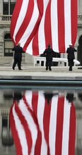 Firefighters are reflected in a fountain at the Empire State Plaza as they lower a flag after a ceremony at the New York State Fallen Firefighters Memorial Tuesday, Oct. 9, 2012, in Albany, N.Y. The names of six firefighters who died in the line of duty were added to the memorial wall. (AP Photo/Mike Groll)