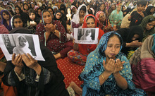 Supporters of Pakistani political party Muttahida Qaumi Movement (MQM), chant prayers in support of 14-year-old schoolgirl Malala Yousufzai, who was shot on Tuesday by the Taliban for speaking out in support of education for women, at the (MQM)' headquarter in Karachi, Pakistan, Wednesday, Oct. 10, 2012. Pakistani doctors successfully removed a bullet Wednesday from the neck of a 14-year-old girl who was shot by the Taliban for speaking out in support of education for women, a government minister said. Writing on the poster under Malala's picture  read,