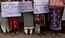 Pakistani women, hold banners during a protest condemning the attack on schoolgirl Malala Yousufzai, in Islamabad, Pakistan, Wednesday, Oct. 10, 2012. Pakistani doctors successfully removed a bullet Wednesday from the neck of a 14-year-old girl who was shot by the Taliban for speaking out in support of education for women, a government minister said. Banner top right reads,