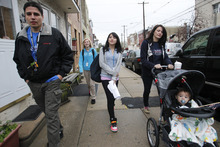 Charles Carroll High School student Samantha Pawlucy, center, arrives at the school Tuesday Oct. 9, 2012, with parents Richard, left, and mother Kristine, pushing son Matthew, in Philadelphia. Supporters of  Pawlucy gathered outside the school to show support for the teen as she returned to school for the first time after she was allegedly mocked by her geometry teacher for wearing a Mitt Romney T-shirt last week. Her father said that Samantha, who never actually made it to class after the rally, and his other high-school age children will be transferring to another school. (AP Photo/Philadelphia Daily News, Alejandro A. Alvarez)