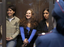 Sergey Ponomarev     The Associated Press Feminist punk group Pussy Riot members, from left, Maria Alekhina, Yekaterina Samutsevich and Nadezhda Tolokonnikova sit in a glass cage at a court room in Moscow, Wednesday. Oct. 10, 2012. On Wednesday, Samutsevich unexpectedly walked free from a Moscow courtroom, but the other two now head toward a harsh punishment for their irreverent protest against President Vladimir Putin: a penal colony.