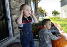 Scott Sommerdorf  |  The Salt Lake Tribune              Damien Cook, left, reacts to the loud noise of the UPS man as he turns around his truck on their street while on the porch with his older brother Christian, Monday, October 1, 2012.