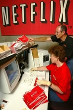 FILE - In this July 11, 2002, file photo, Netflix co-founder Marc Randolph looks over the shoulder of Natalya Kontorovich at Netflix Inc.'s Denver distribution site. A new book,