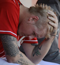 Cincinnati Reds starting pitcher Mat Latos sits in the dugout after giving up a grand slam to San Francisco Giants' Buster Posey in the fifth inning of Game 5 of the National League division baseball series, Thursday, Oct. 11, 2012, in Cincinnati. (AP Photo/Michael Keating)