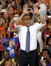 President Barack Obama does the sign of