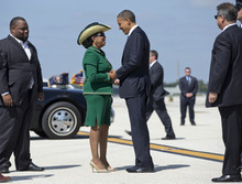 President Barack Obama is greeted by Rep. Frederica Wilson, D-Fla., center, and Florida State Rep. Dwight Bullard, left, as he steps off of Air Force One at Miami International Airport, Thursday, Oct. 11, 2012, in Miami. (AP Photo/Carolyn Kaster)