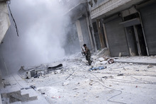 In this Wednesday, Oct. 10, 2012 photo, a Free Syrian Army fighter looks for cover after firing his weapon against Syrian Army positions in the Karmal Jabl district in Aleppo, Syria. (AP Photo/ Manu Brabo)