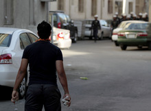 A Bahraini anti-government protester holds stones as he waits to confront approaching riot police during clashes after police dispersed a march through narrow market streets of the capital of Manama, Bahrain, on Friday, Oct. 12, 2012. Riot police in Bahrain fired tear gas and stun grenades to disperse hundreds of protesters in the capital of the restive Gulf kingdom and arrested several people. (AP Photo/Hasan Jamali)