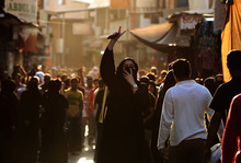 A Bahraini anti-government protester gestures toward riot police, unseen, as she covers her face against tear gas in the narrow market streets of the capital of Manama, Bahrain, on Friday, Oct. 12, 2012. Riot police in Bahrain fired tear gas and stun grenades to disperse the hundreds of protesters in the capital of the restive Gulf kingdom and arrested several people. (AP Photo/Hasan Jamali)