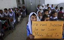 Pakistani girls display a poster while sitting at their desk, as their teacher, not shown, talks to them about 14-year-old schoolgirl Malala Yousufzai, who was shot on Tuesday by a Taliban gunman for her role in promoting girls' education in the Swat Valley where she lives, in a school in Islamabad, Pakistan, Friday, Oct. 12, 2012. A Pakistani military spokesman says Yousufzai is in