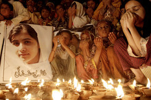 Pakistani children pray for the recovery of 14-year-old schoolgirl Malala Yousufzai, who was shot on Tuesday by the Taliban for speaking out in support of education for women, during a candlelight vigil in Karachi, Pakistan, Friday, Oct. 12, 2012. A Pakistani military spokesman says Yousufzai is in
