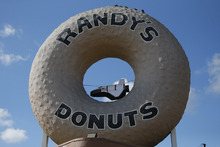 In this Wednesday, Oct. 10, 2012 photo, an inflatable space shuttle Endeavour hangs from a sign at Randy's Donuts in Los Angeles. Beginning Friday, the shuttle heads off on its last mission, a 12-mile creep through city streets. It will move past an eclectic mix of strip malls, mom-and-pop shops, tidy lawns and faded apartment buildings. Its final destination: California Science Center in South Los Angeles where it will be put on display. (AP Photo/Jae C. Hong)