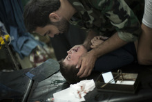 In this Wednesday, Oct. 10, 2012 photo, a Free Syrian Army fighter comforts a child wounded by Syrian Army artillery shelling, at Dar El Shifa hospital in Aleppo, Syria. (AP Photo/ Manu Brabo)