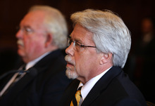 FILE - In this Oct. 9, 2012 file photo, Mark Strong Sr., right, sits with his attorney Dan Lilley, left, during his arraignment in Portland, Maine on 59 charges, including promotion of prostitution and violation of privacy in connection with a Kennebunk Zumba dance studio. A lawyer for two alleged clients of a Maine woman accused of running a prostitution business out of her Zumba dance studio and secretly videotaped the encounters has filed a motion to block the release of names of the men suspected as her clients. (AP Photo/Joel Page, File)