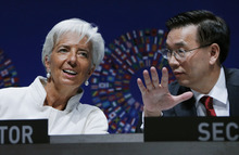 International Monetary Fund Managing Director Christine Lagarde, left, speaks with IMF Corporate Secretary Lin Jianhai at the opening of the annual meetings plenary of IMF and World Bank Group in Tokyo, Friday, Oct. 12, 2012. (AP Photo/Koji Sasahara)