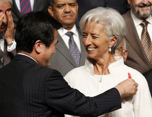 International Monetary Fund Managing Director Christine Lagarde, right, smiles as Japanese Finance Minister Koriki Jojima puts a red feather for the community chest on her jacket during the governors family photo session at the annual meetings plenary of the IMF and World Bank Group in Tokyo Friday, Oct. 12, 2012. (AP Photo/Koji Sasahara)