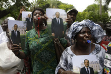 Senegalese women wave photographs of French President Francois Hollande, as he arrives at the Presidential Palace in Dakar, Senegal, Friday, Oct. 12, 2012. Hollande will attempt to make right France's relationship with Africa on his first visit to the continent on Friday, beginning with a stop in Senegal, the seat of France's former colonial empire. He is set to leave Friday night for Congo, where he will attend the Francophonie summit in the capital, Kinshasa. (AP Photo/Rebecca Blackwell)