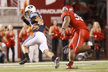 Chris Detrick  |  The Salt Lake Tribune Brigham Young Cougars quarterback Riley Nelson (13) runs away from Utah Utes defensive tackle Star Lotulelei (92) during the first half of against BYU at Rice-Eccles Stadium Saturday September 15, 2012.