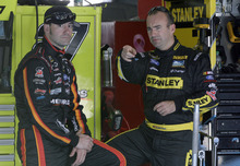 Drivers Marcos Ambrose, right, and Paul Menard, left, talk before practice for Saturday's NASCAR Bank of America 500 Sprint Cup series auto race in Concord, N.C., Friday, Oct. 12, 2012. (AP Photo/Chuck Burton)