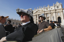 A nun wears a hat made with newspaper pages as she waits for Pope Benedict XVI to celebrate a Mass marking the 50th anniversary of the Second Vatican Council, in St. Peter's Square at the Vatican, Thursday, Oct. 11, 2012. Benedict, after celebrating Mass, will greet churchmen, including a dozen original Vatican II participants, re-enacting the great procession into St. Peter's that launched the council in 1962. (AP Photo/Andrew Medichini)